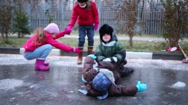 Girls and boys play on frozen puddle