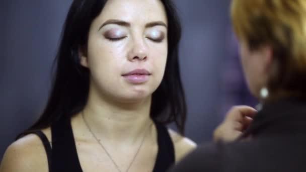 Vizážistiku dává make-up pomocí štětce na horní víčko modelu