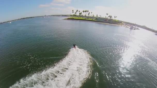 Muž letí na vodním paprskem v zátoce plachty