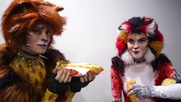 Muž a žena v kostýmech kočky jíst