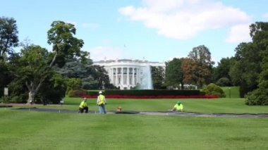 Workers on green lawn near White House
