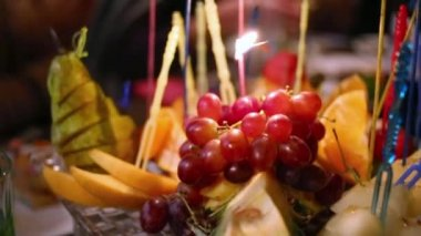 Plate with fruits and burning birthday candles