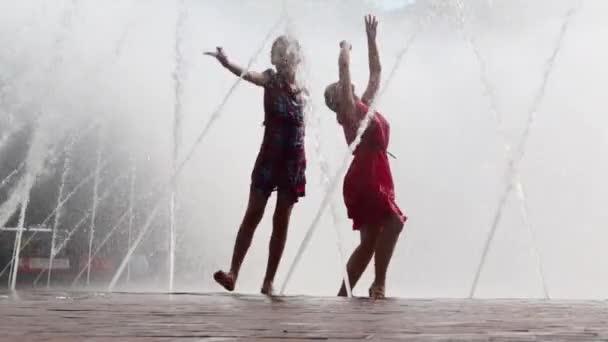 Mutter und Tochter tanzen im Brunnen