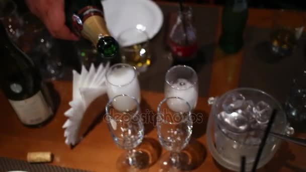 Hand pours sparkling wine into wineglasses