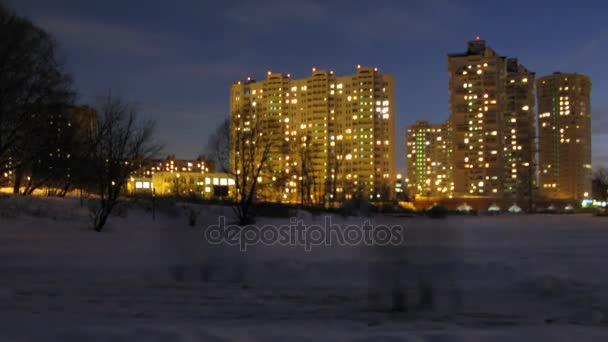 People clean the snow not far from residential buildings