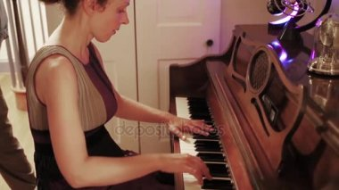 Beautiful young woman is playing on the vintage piano.