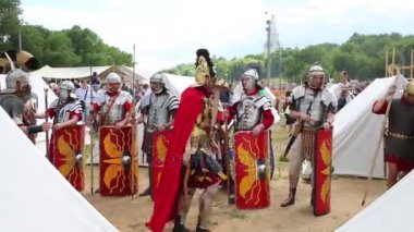 MOSCOW - JUNE, 6, 2015: Mens dressed in armor Roman legionary with shield on historical festival in Kolomenskoye. In summer, in framework of historical festival Times and Epochs revived Roman Empire.