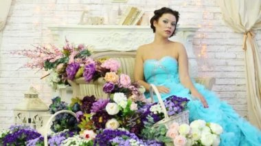 A woman in a blue dress sitting on a chair, picks up a bouquet of flowers and bring it to the face