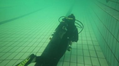 Back of diver in wetsuit with scuba swimming on bottom of pool
