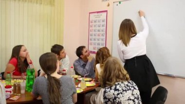 Nine teenagers sit at table and play game in classroom, girl draws on board. Text: English alphabet, 2 words