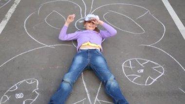 Lány fekszik a nagy pillangó rajzolta kréta aszfalt