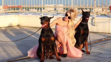 Pretty young woman poses with two dogs of roof of tall building