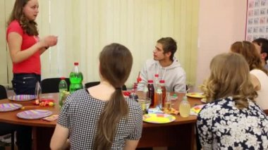 Six teenagers sit at table and play pantomime game at birthday, girl depicts object