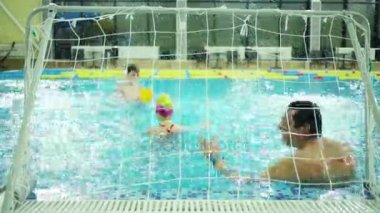 Father and two children play water soccer in indoor pool