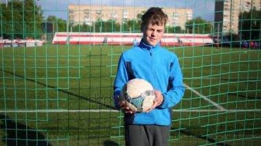 Boy hází a kope fotbalový míč s kolenem na stadionu