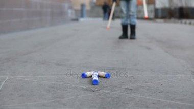 Legs boy throwing twice large sticks to arrow on asphalt in game gorodki.