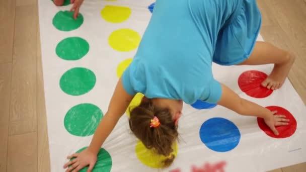 Chlapec a dívka hru Twister na podlaze v pokoji domova