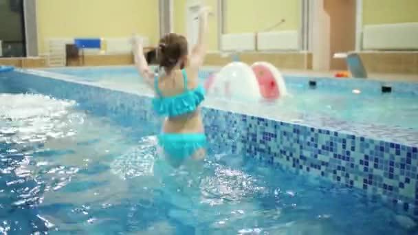 Malé radostné holčičky v modré plavky tance v bazénu a boy plave poblíž she