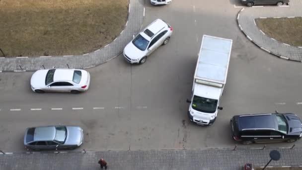 Pohled shora zaparkovaných aut a pohyblivé bílé van na asfaltu