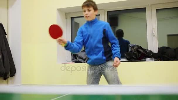 Šťastný chlapec dospívající v modrém hraje stolní tenis vnitřní