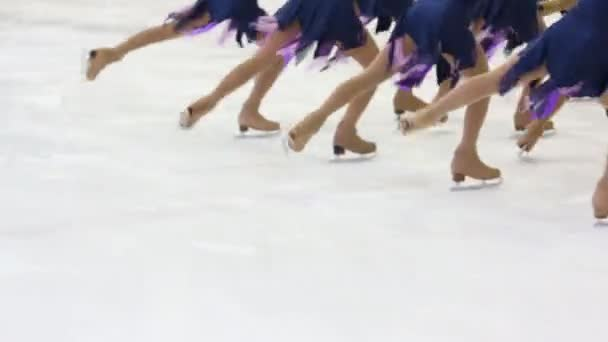 Legs of graceful girls team skating on ice rink during competition