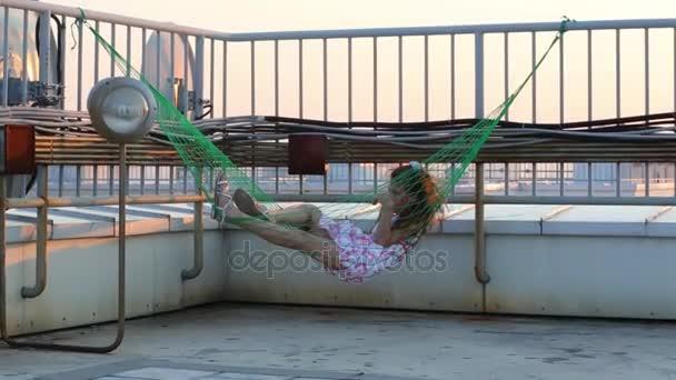 Petite Fille Allongé Dans Hamac Tendu Sur Clôture Sur Toit Vidéo
