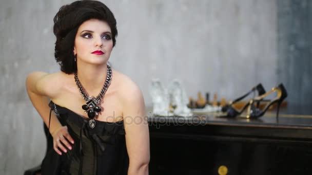 Hezká žena v černých šatech představuje poblíž grand piano