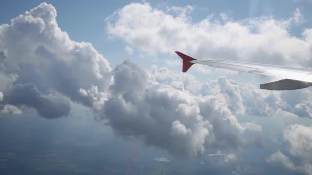 Část křídla a bílé haldy mraky prostřednictvím okénka z uvnitř letounu