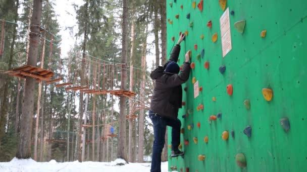 Mann klettert an Wintertag auf Spezialwand zum Klettern