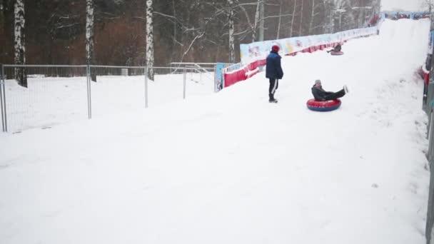 Glückliche Menschen, die am Wintertag auf Schneeröhren den Hang hinunterfahren