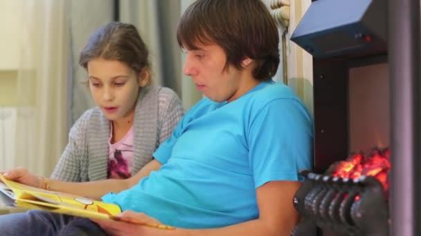 Un uomo che legge un libro per bambini con la ragazza accanto al caminetto