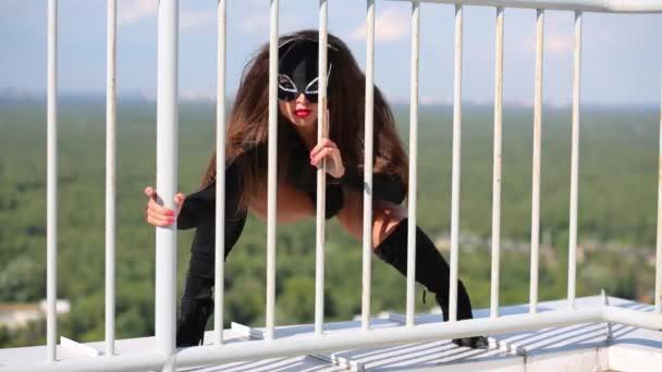 Katze im schwarzen Kostüm posiert hinter Geländer auf Dach