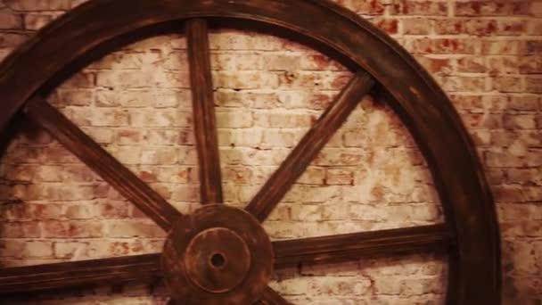 Velké dřevěné retro dekorativní kolo u cihlové zdi ve studiu