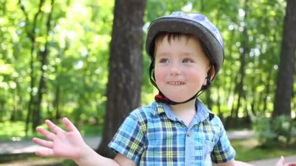 Boldog aranyos kisfiú sisak taps a nyári park
