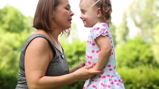 Little happy girl and her mother touch noses of each other in park