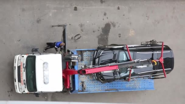 Top view of modern tow truck loading broken black car