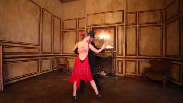 Dívka v červených šatech a muž v černém obleku tanec tango krbu