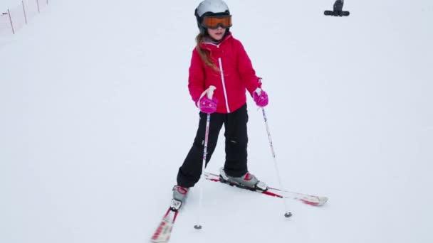 Šťastná dívka v představuje sluneční brýle na lyžování na svahu lyžařského střediska