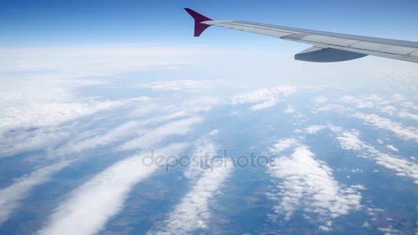 Křídla a bílá cirokumulus Mraky prostřednictvím okénka z uvnitř letounu