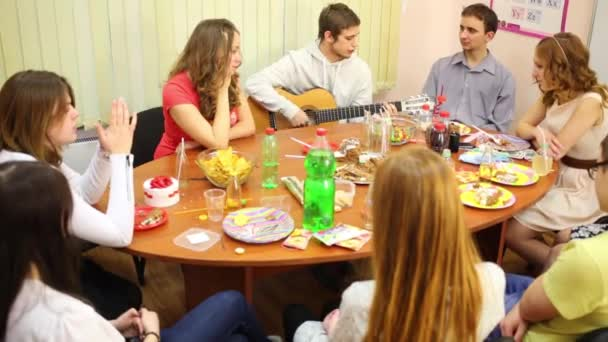 Boy teenager plays guitar and eight friends listen him in room