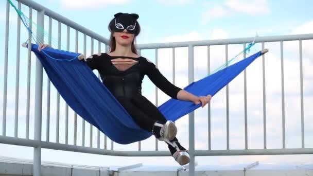 Hübsche Frau im Katzenkostüm schaukelt in Hängematte auf Dach und verschwindet
