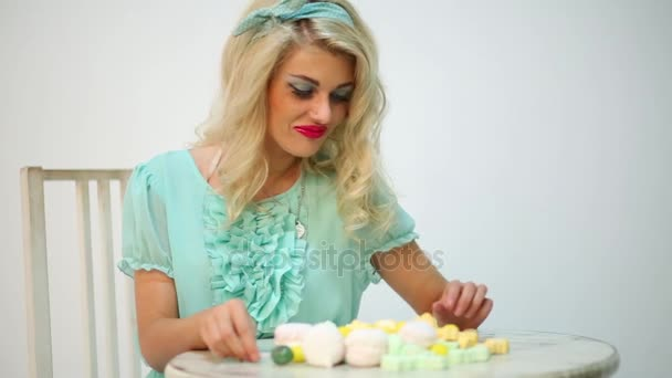 Beautiful girl with white hair with lollipop looking at marshmallows