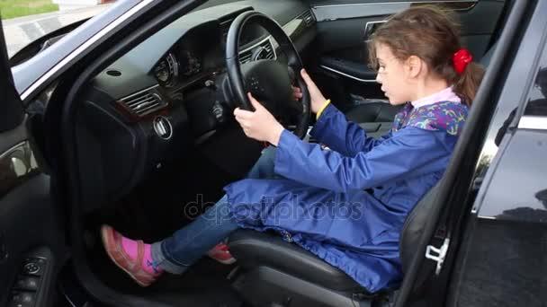 Lány ül az autóban, a kézen a kerék vezetőülés