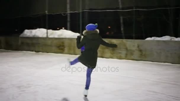 Teen dívka půvabné Bruslení na kluzišti v zimní noci
