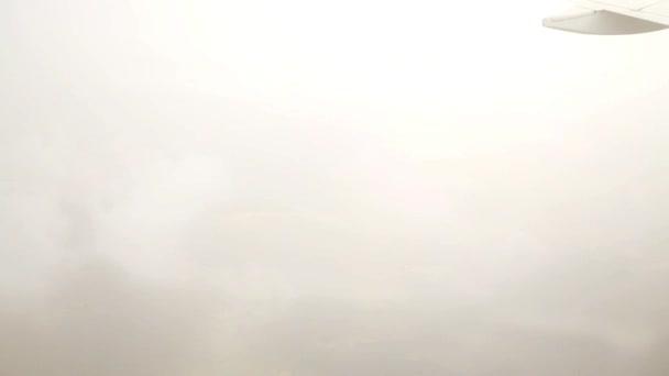 Letadlo letí z oblak, pohled z uvnitř kabiny letadla