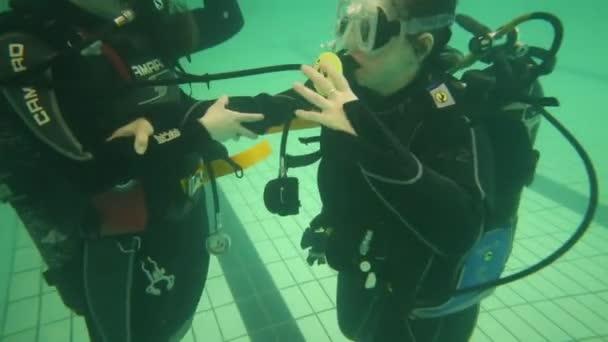 Moskva – 11. dubna 2015: Dívka a žena v neopren Camaro na dně bazénu. Rakouská společnost Camaro - více než 40 let na trhu potápěčského vybavení a vybavení pro potápění