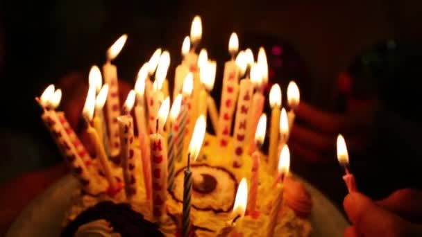 Cake with burning candles in dark close up and people around.