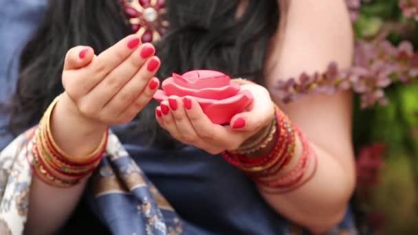 Nahaufnahme eines Womans Hand mit erloschenen Kerzen in Form von Rosen.