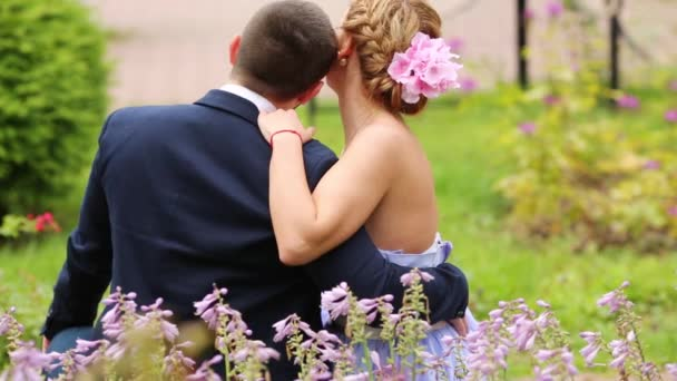 Couple sitting back and embracing nestling together among flowers on grass in park.