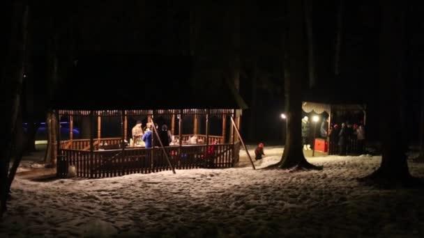 Noční zimní pohled ze dvou dřevěných pergol s lenoškou lidí
